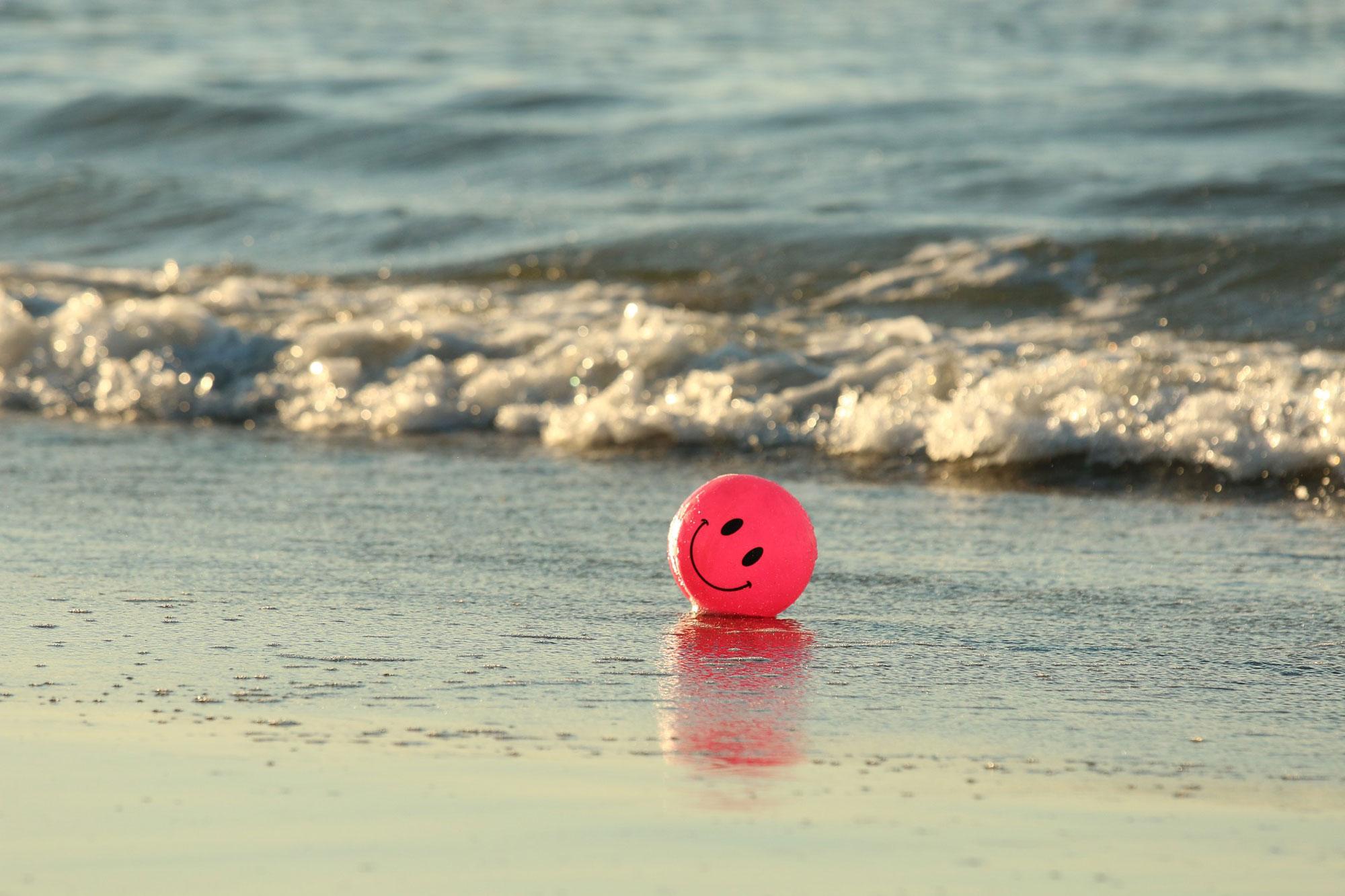 Pinker Luftballon mit Smile-Gesicht am Strand.
