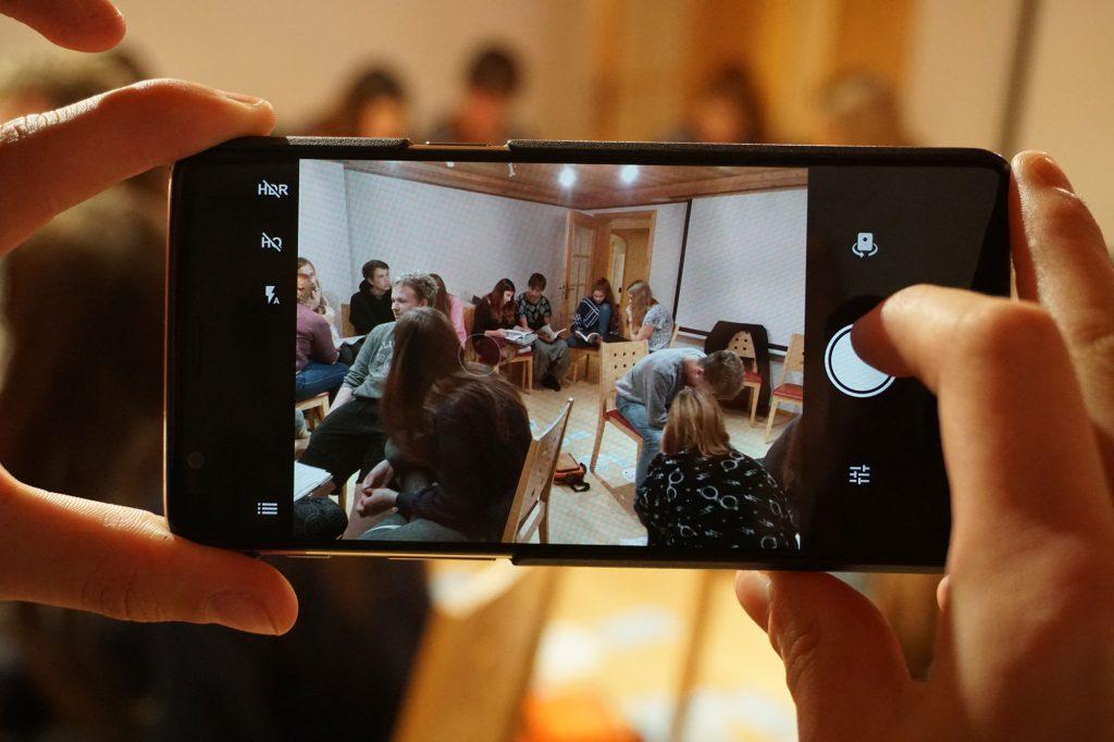 Durch Handy-Kamera werden Jugendliche in einem Raum aufgenommen.
