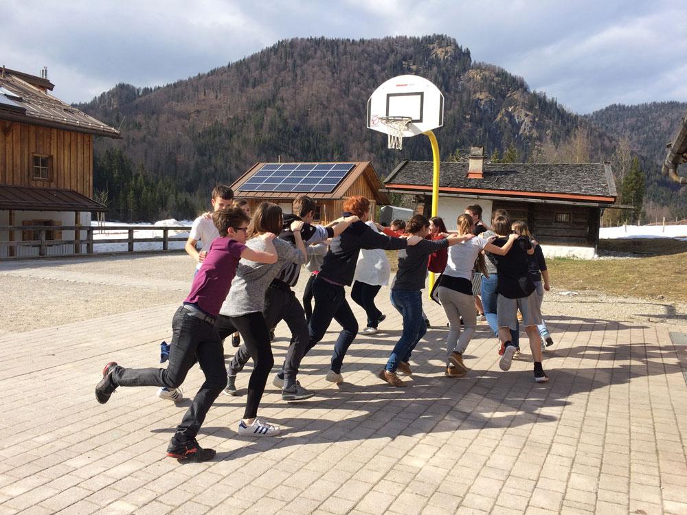 Jugendliche fassen sich an die Schultern auf Basketballplatz vor Bergkulisse
