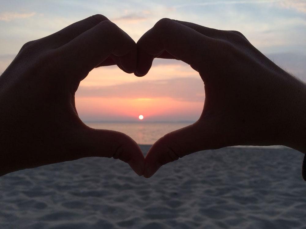Sonnenuntergang durch in Herzforn gefaltete Hände betrachtet.