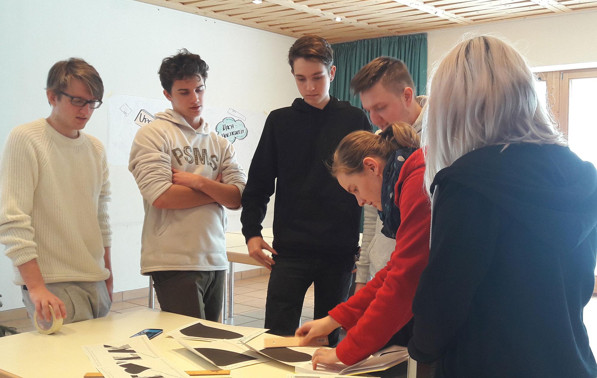 """Mitglieder des Leitenden Kreises beim Arbeitstreffen in Siegsdorf: Jugendliche und Erwachsene scharen sich um einen Tisch und begutachten Basteleien zum Konventsthema """"Upcycling""""."""
