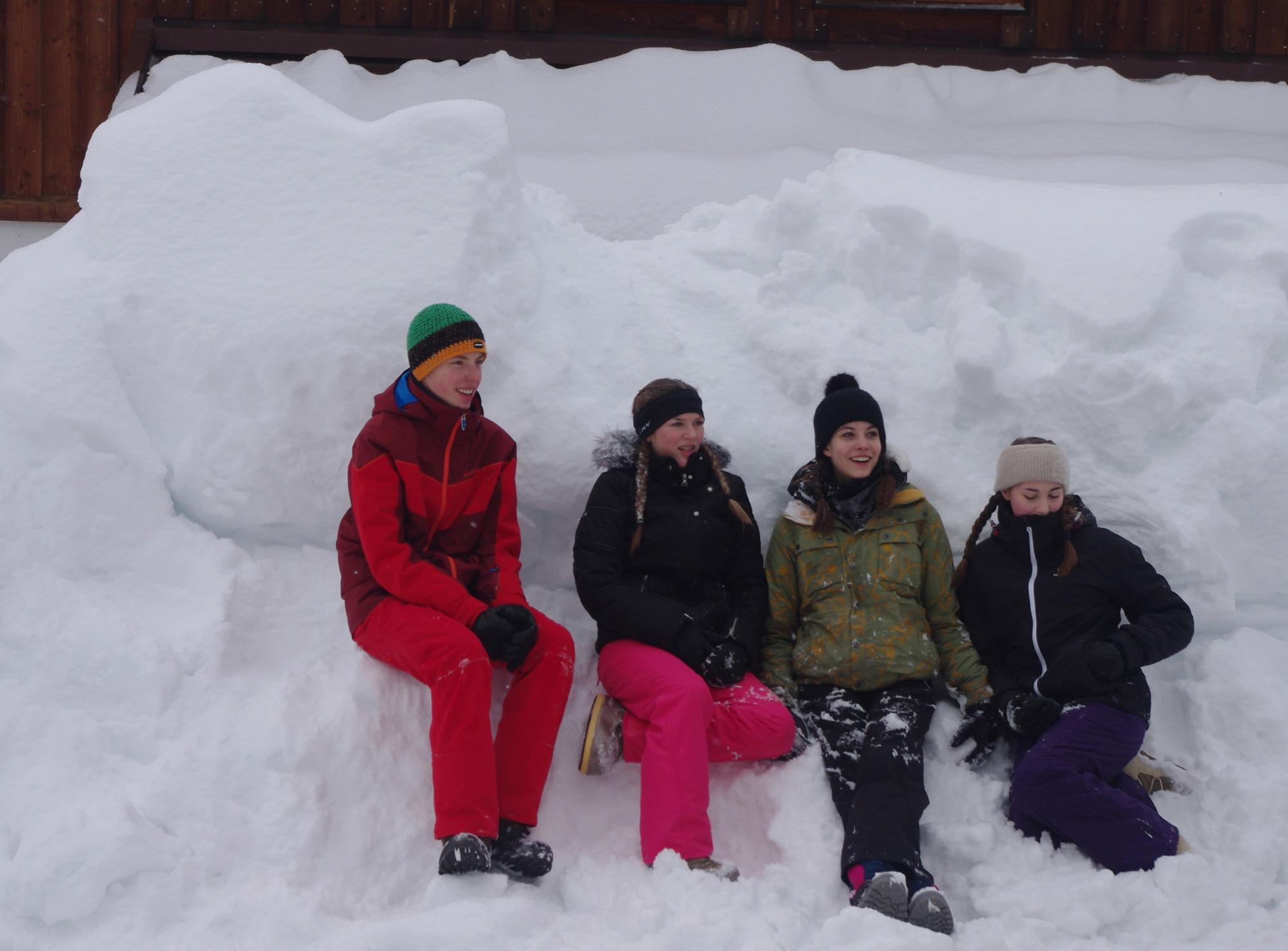 Vier Jugendliche sitzen vor dem Jugendbildungshaus Wiedhölzkaser im Schnee
