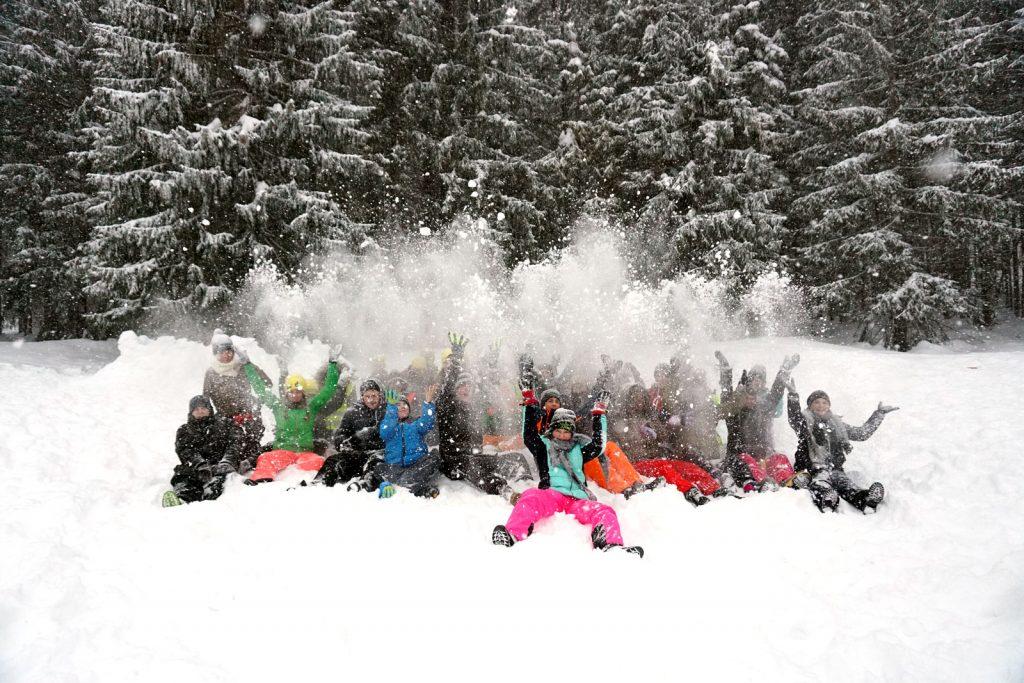 Gruppe von Jugendlichen werfen im sitzen gemeinsam Schnee in die Luft
