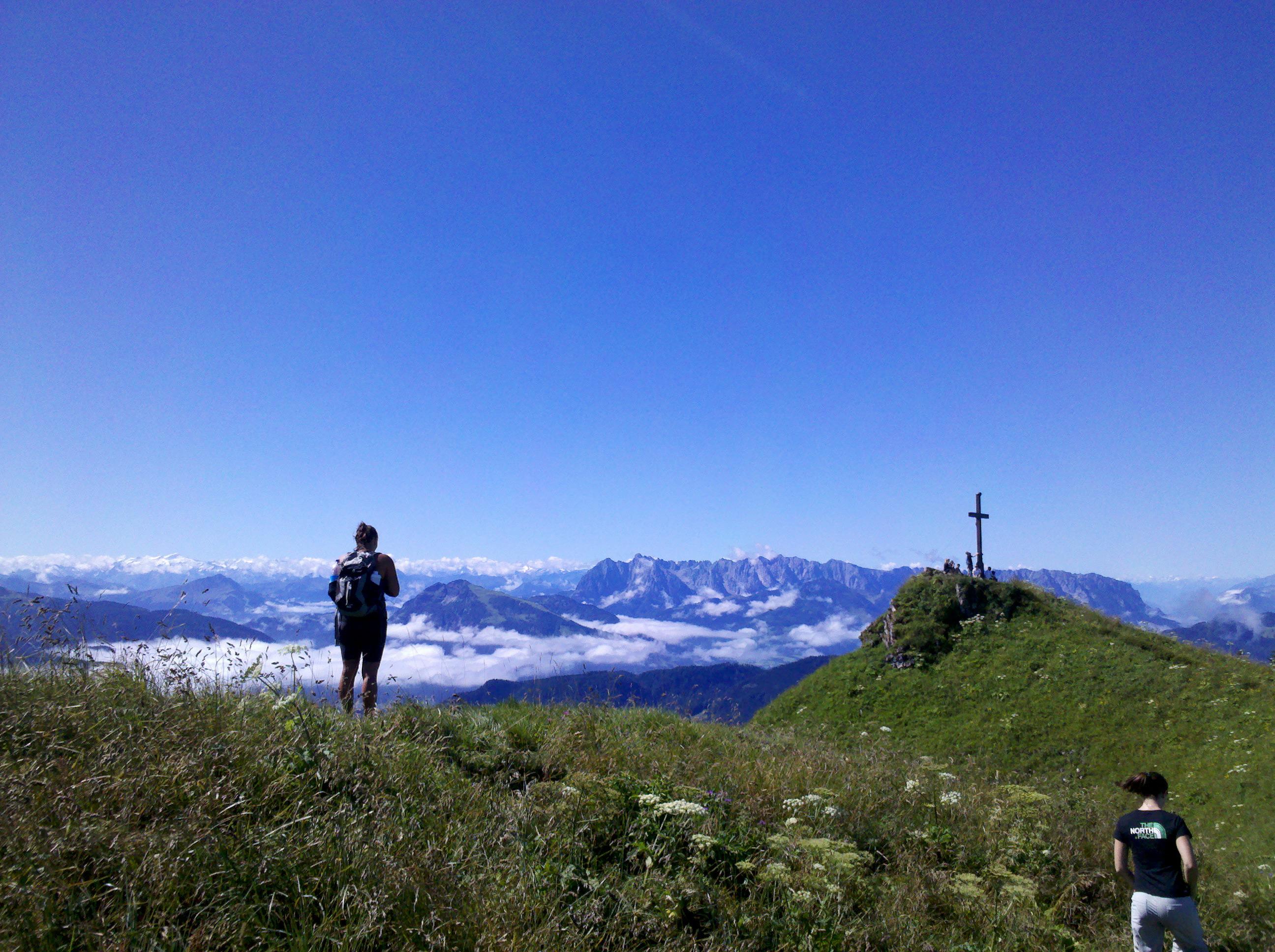 Jugendliche stehen auf Bergwiese mit Gipfelkreuz vor Bergpanorma