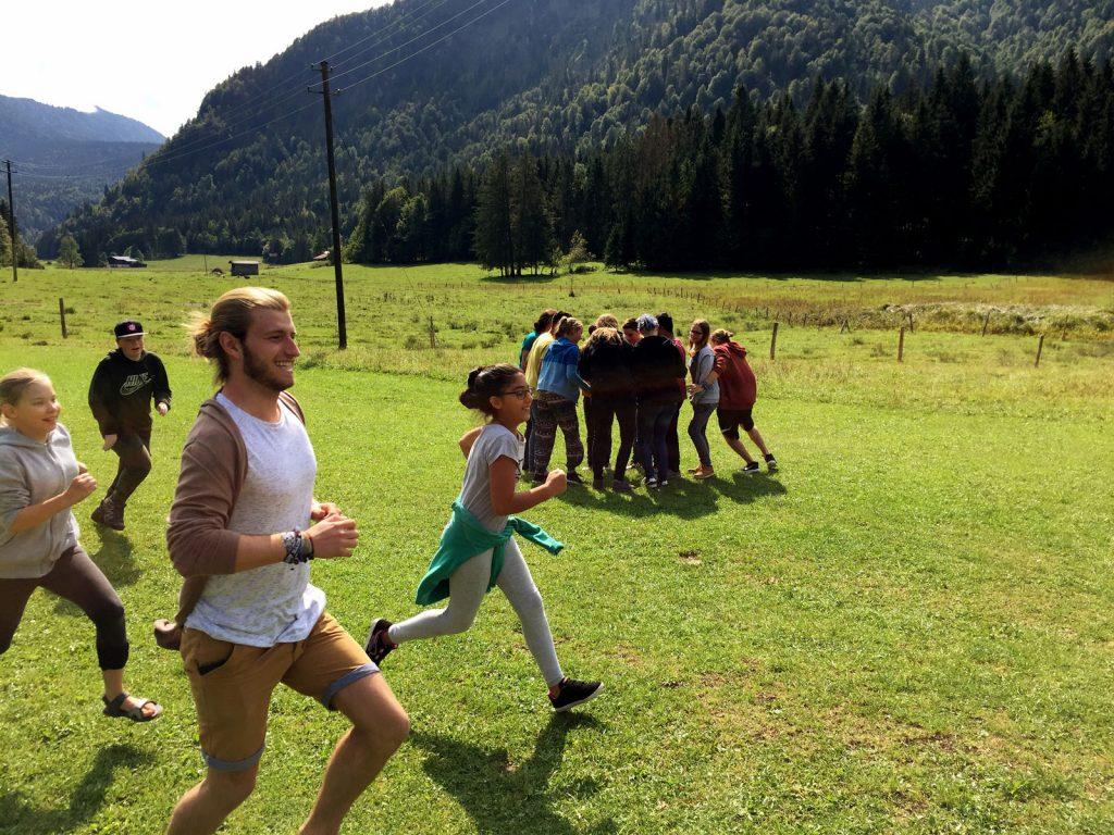 Jugendleiter läuft vor Bergpanorama mit Kindern über eine Wiese
